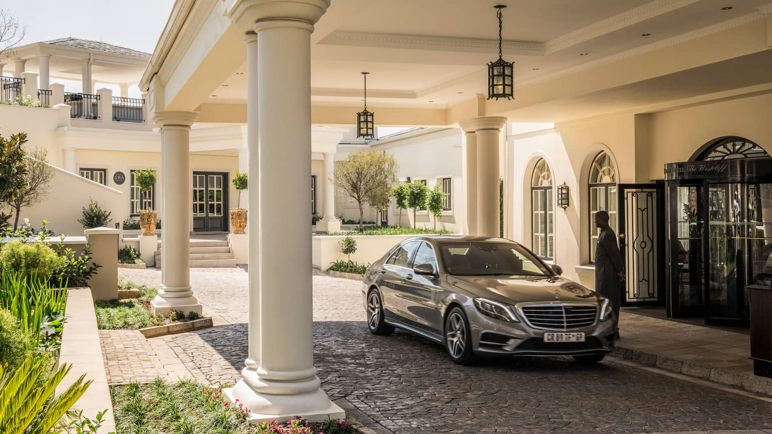 Man greets luxury car under white pillars at front entrance to Four Seasons Hotel The Westcliff, Johannesburg