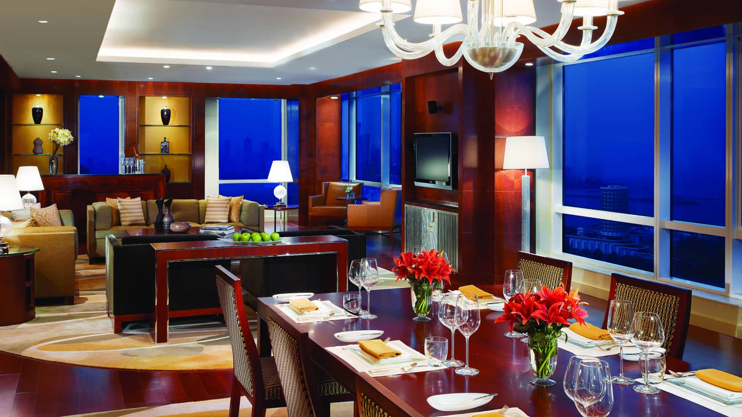 Presidential Suite long dining table under chandelier, seating area, corner windows at night