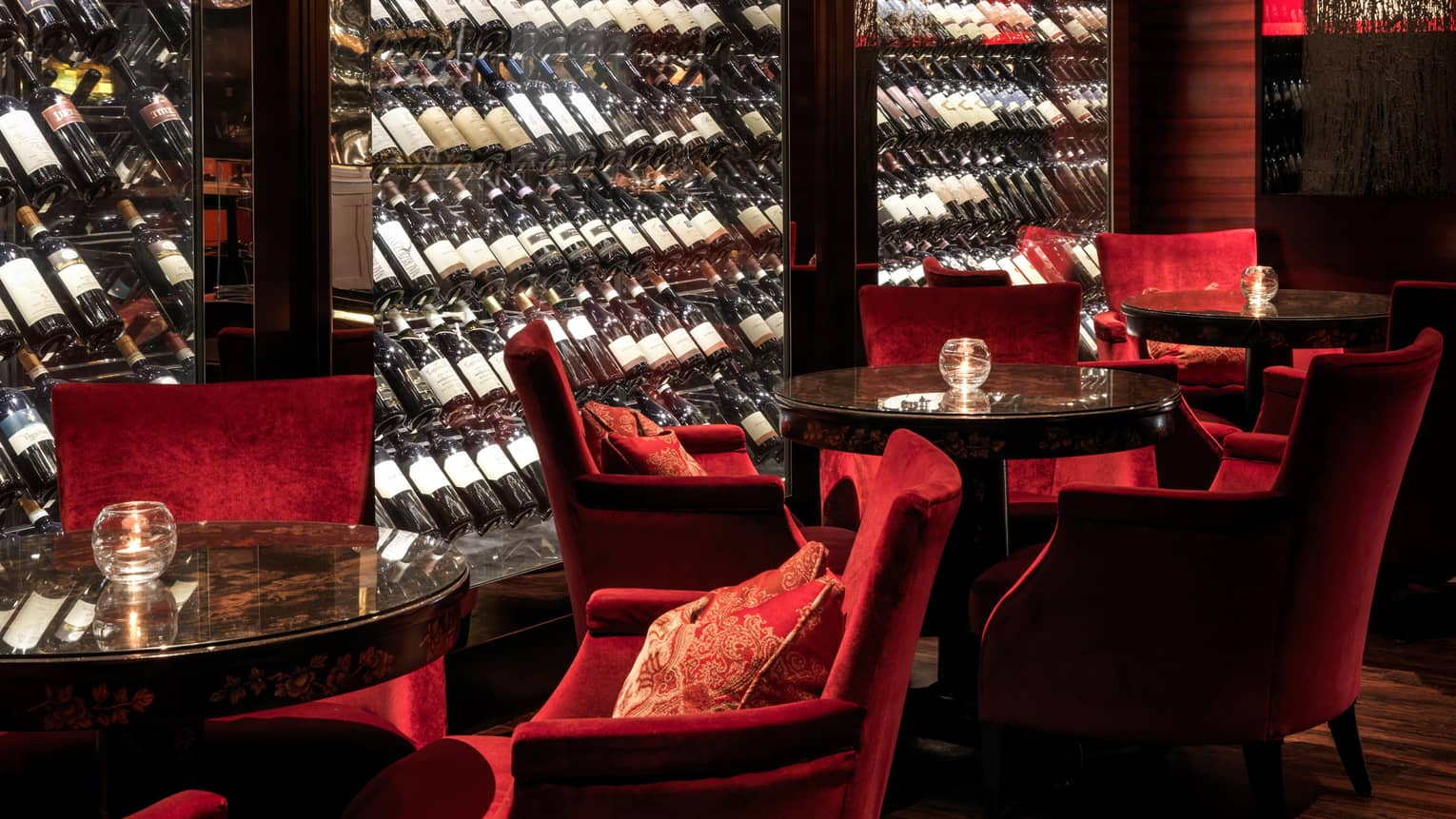 Close-up of Amaranto Bar red velvet lounge chairs by glass cellar, bottles