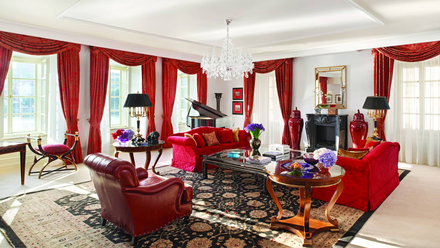 Presidential Suite with red sofas and armchair, red curtains on sunny corner windows, crystal chandelier