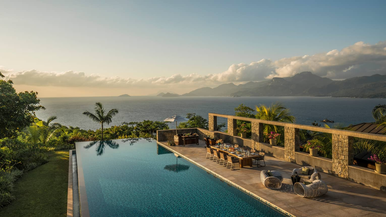 Infinity pool overlooking ocean with palm trees, table, chairs and lounge area