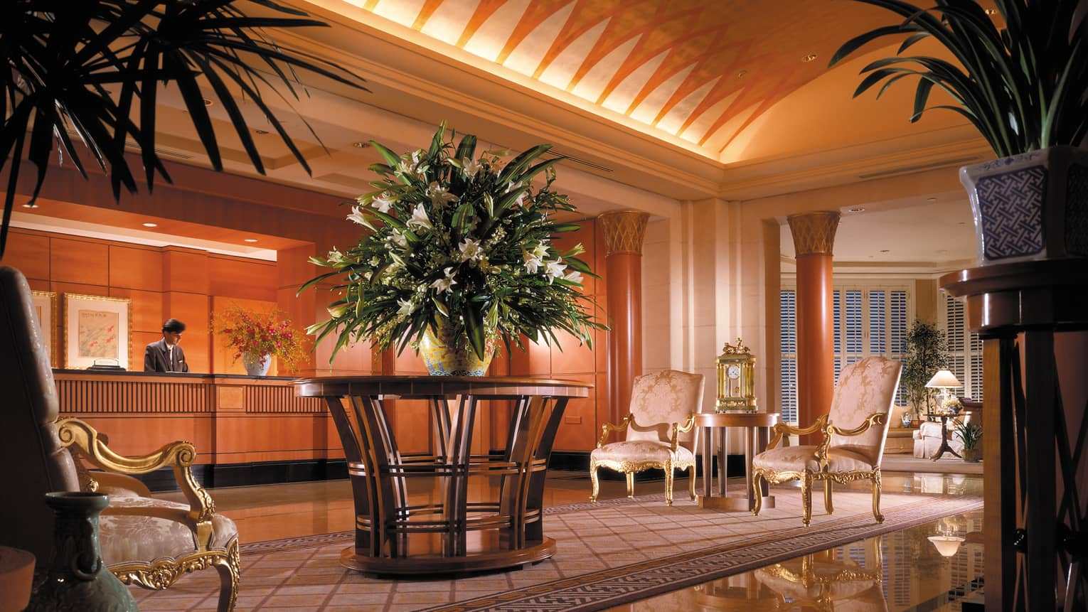Large vase with flowers in hotel lobby with antique-style pink chairs with gold trim