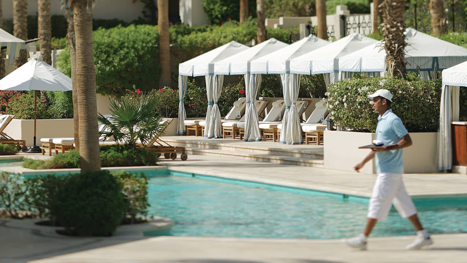 Server in uniform carries tray past outdoor swimming pool, white cabanas on sunny patio in background