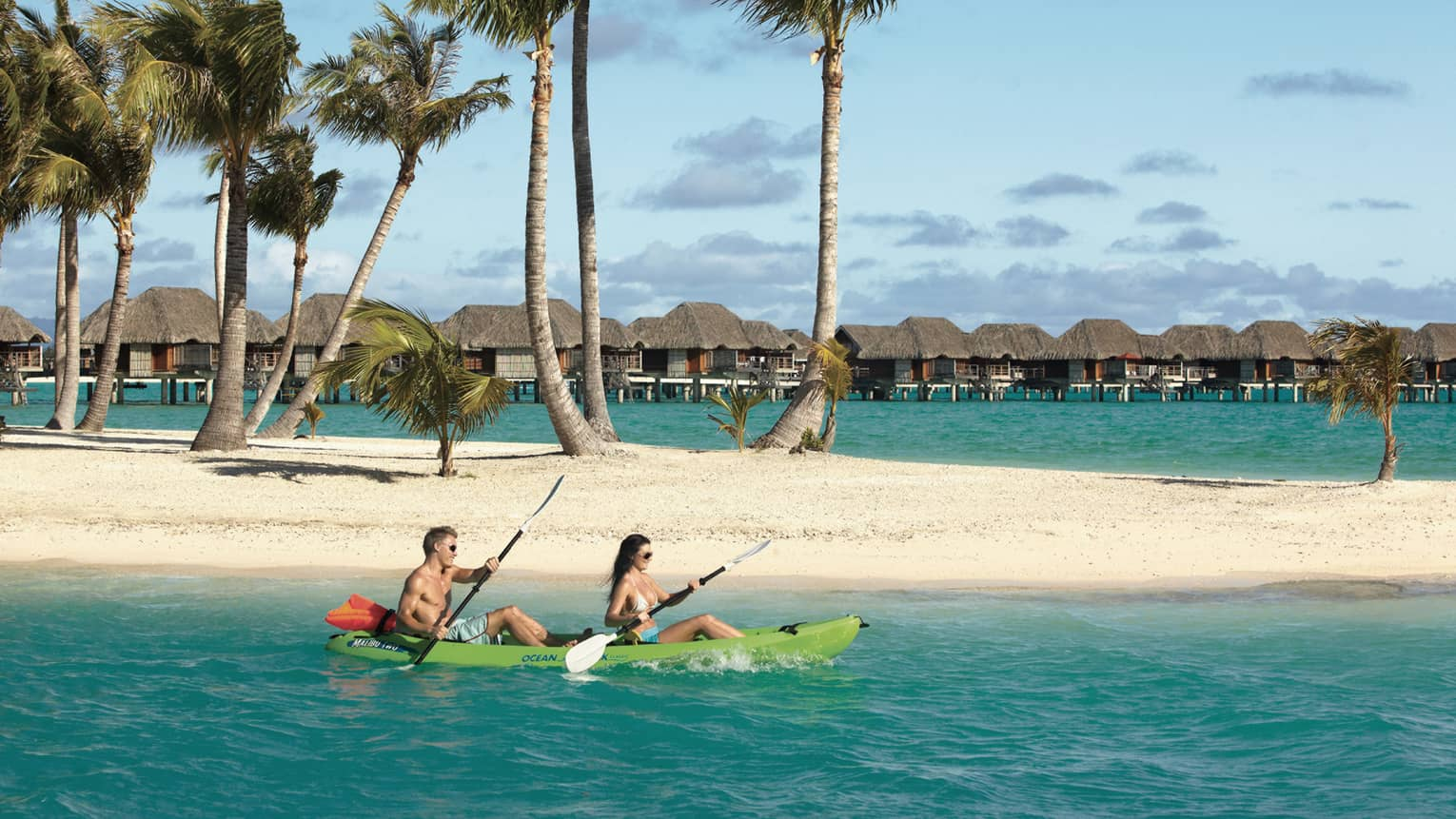 Two guests kayak on a Bora Bora lagoon