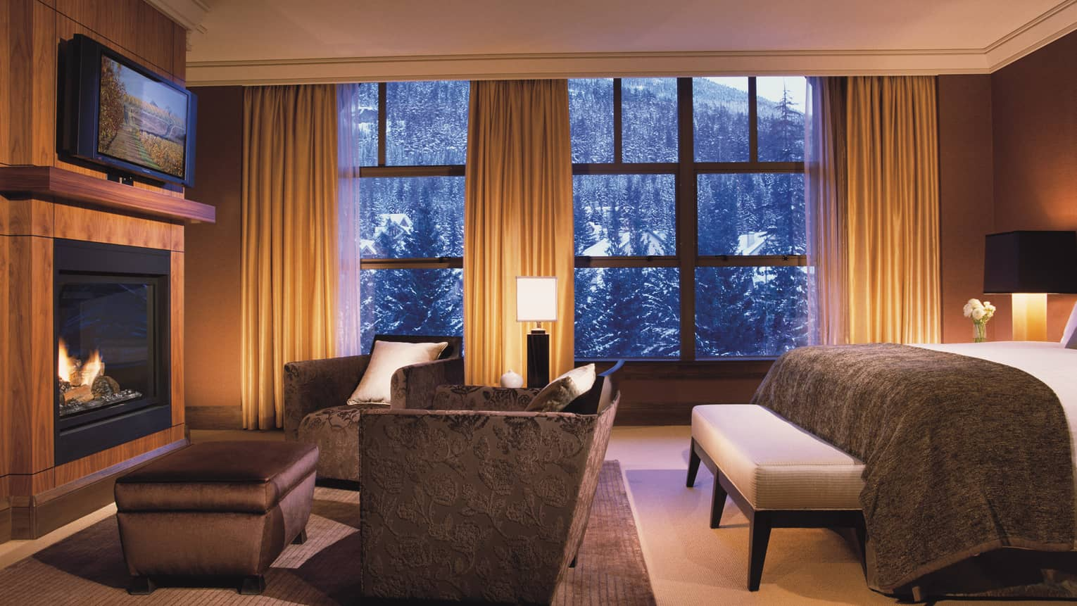 Edge of hotel room bed, sofa and ottoman facing TV and gas fireplace, snowy mountain views from window