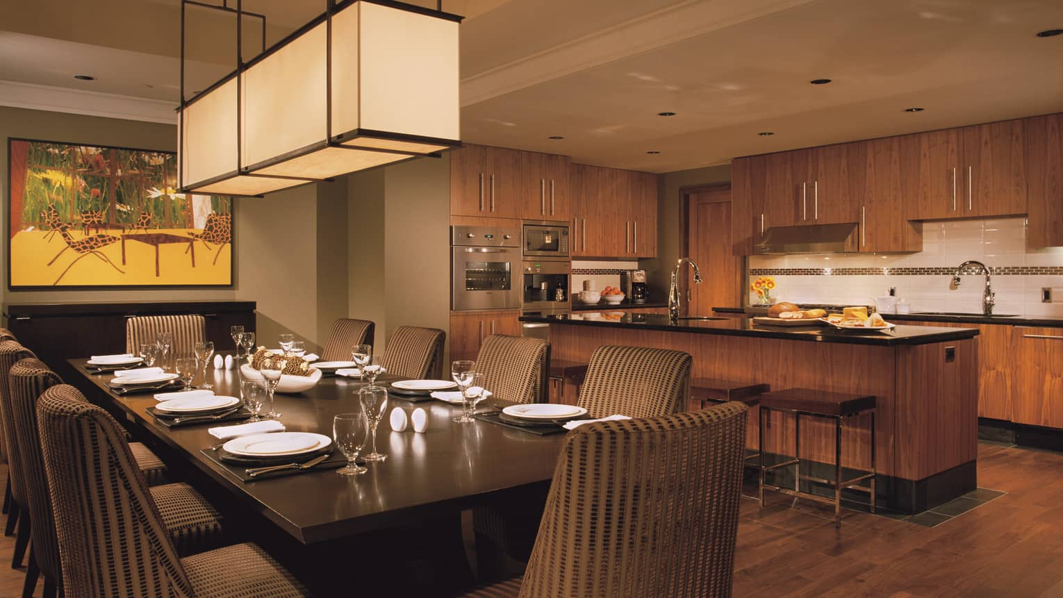 Long lantern chandelier over private dining table in front of kitchen counter with bread, cheese