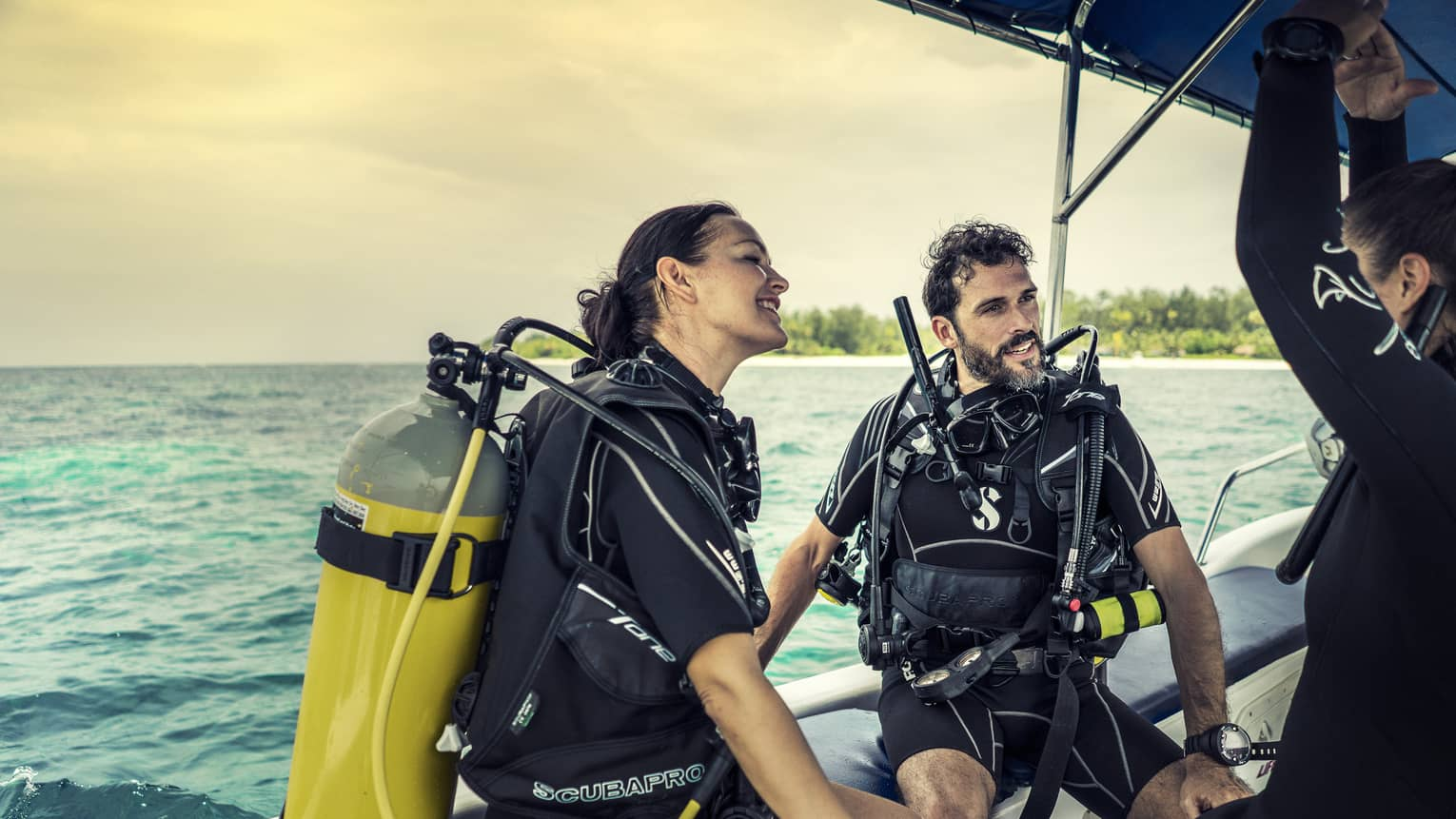 Three people in scuba gear on a boat.