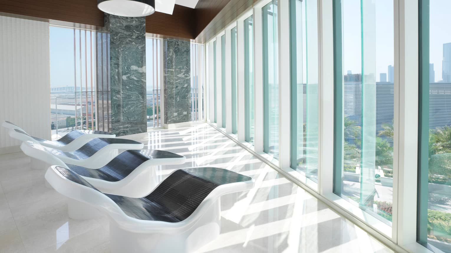 White-and-black recliners in front of floor-to-ceiling glass windows in bright relaxation room
