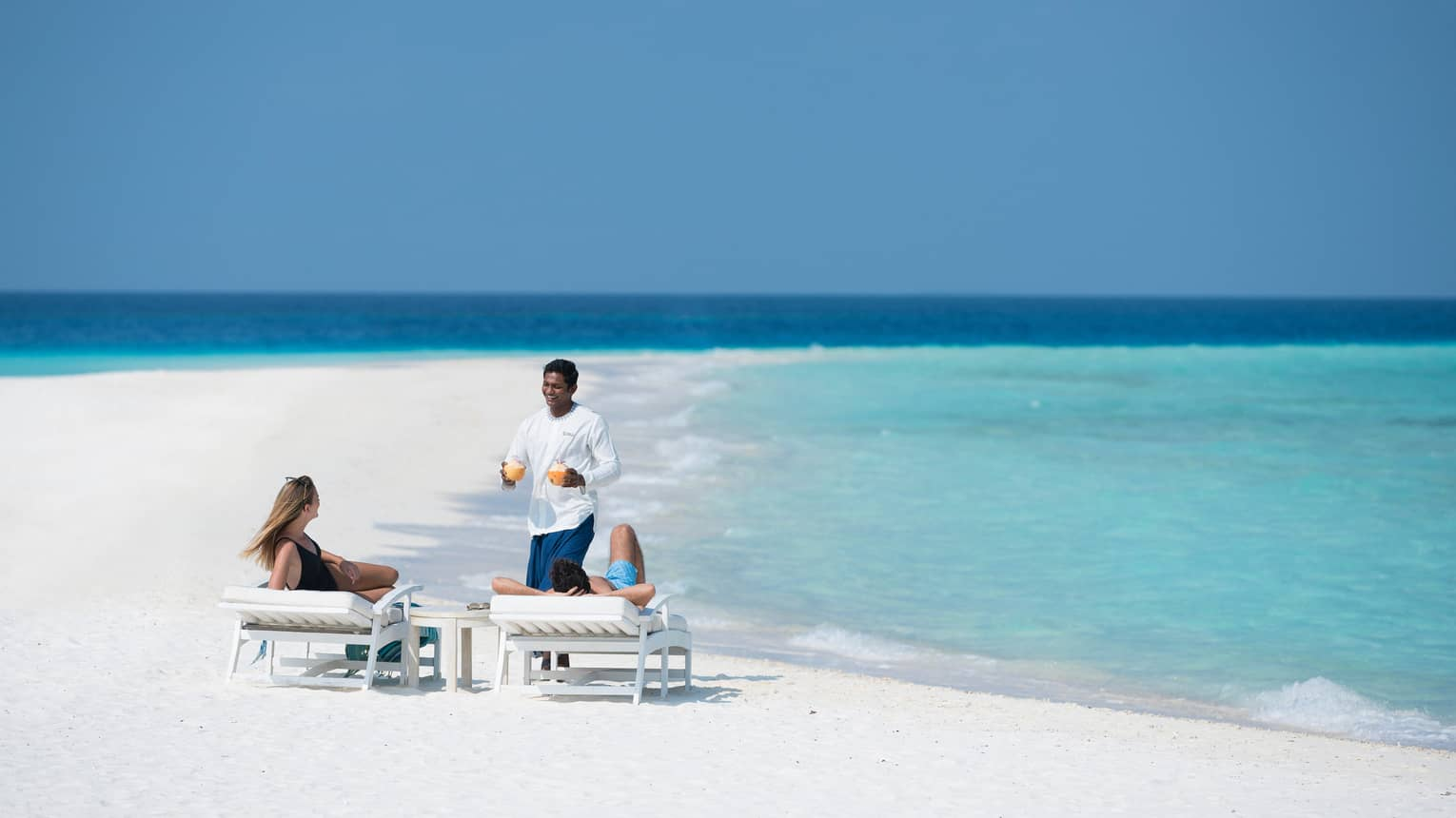 Server brings fresh juice to couple relaxing on lounge chairs on white sand beach by ocean