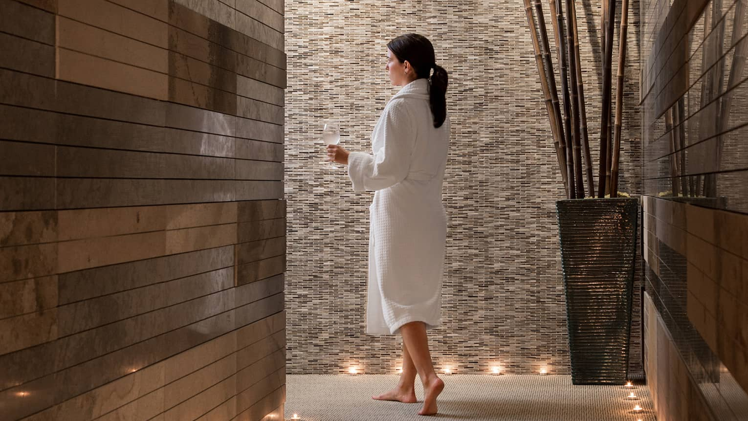 Woman in bathrobe holding wine glass with water walks through spa
