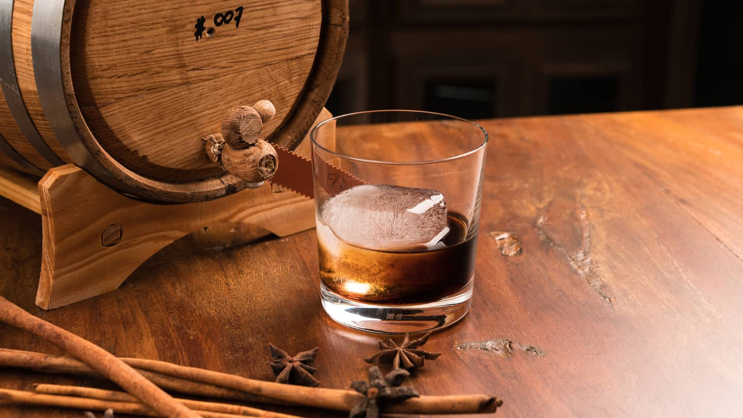 Rock glass with large ice cube, ounce of dark rum in front of small wood barrel on bar