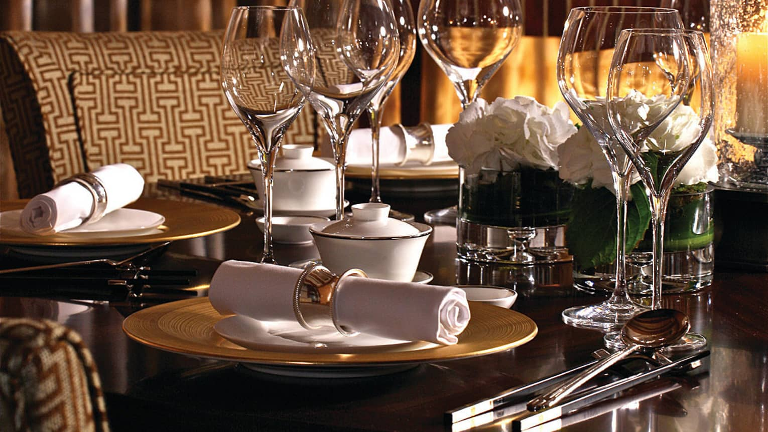 Close-up of dining table with empty wine glasses, place settings, cutlery rolled in white napkin
