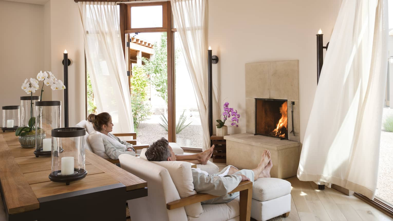 Man, woman in white bathrobes relax on spa armchairs by fireplace, white curtains