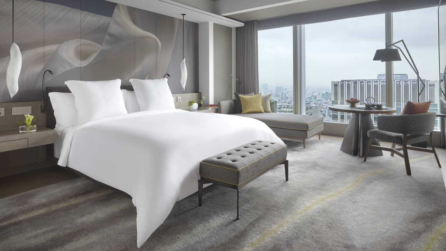 Modern bedroom with Four Seasons king bed, with floor-to-ceiling windows overlooking the city