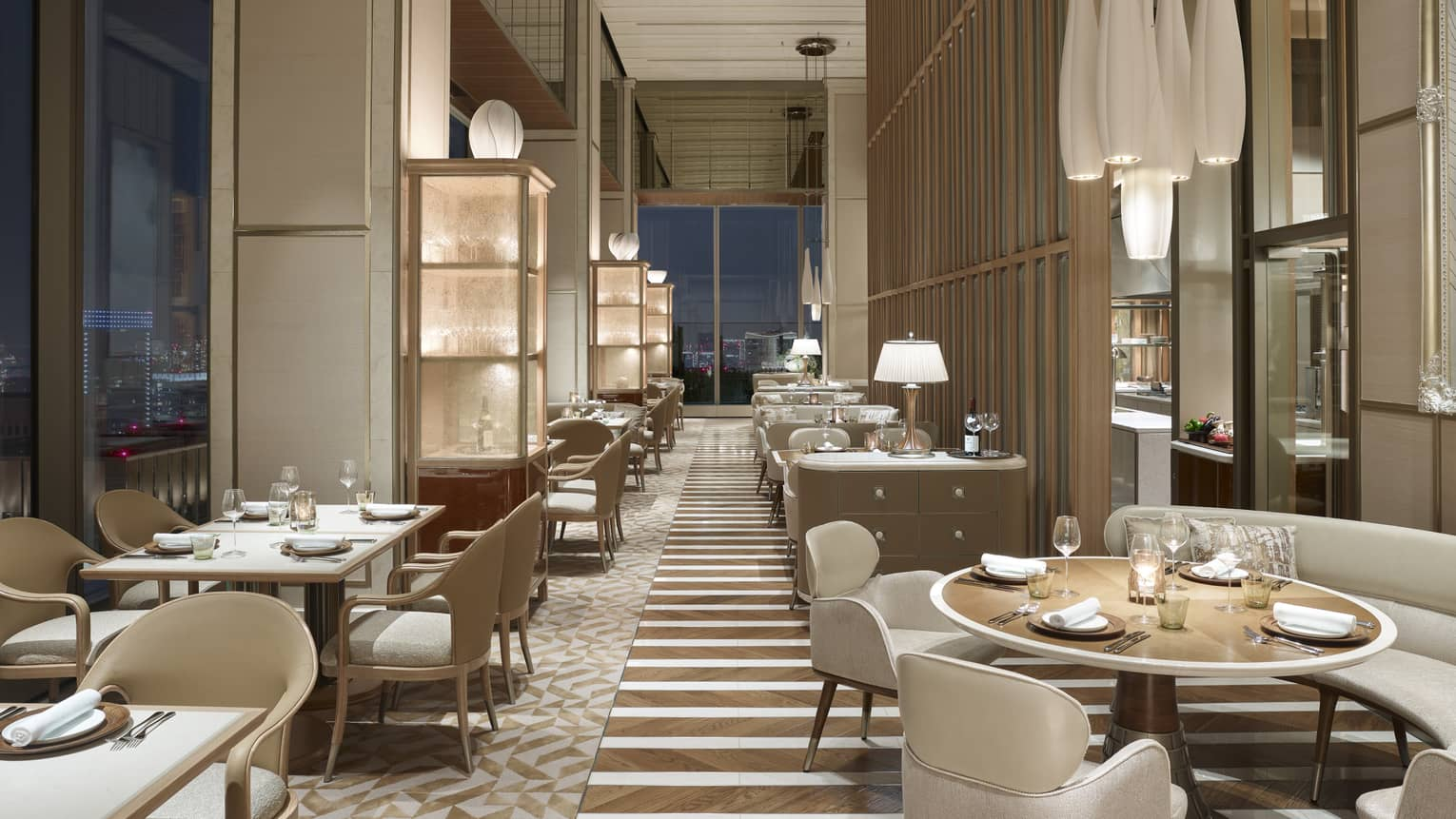 Restaurant with off-white chairs and sofas, elegant chandeliers, windows with nighttime views