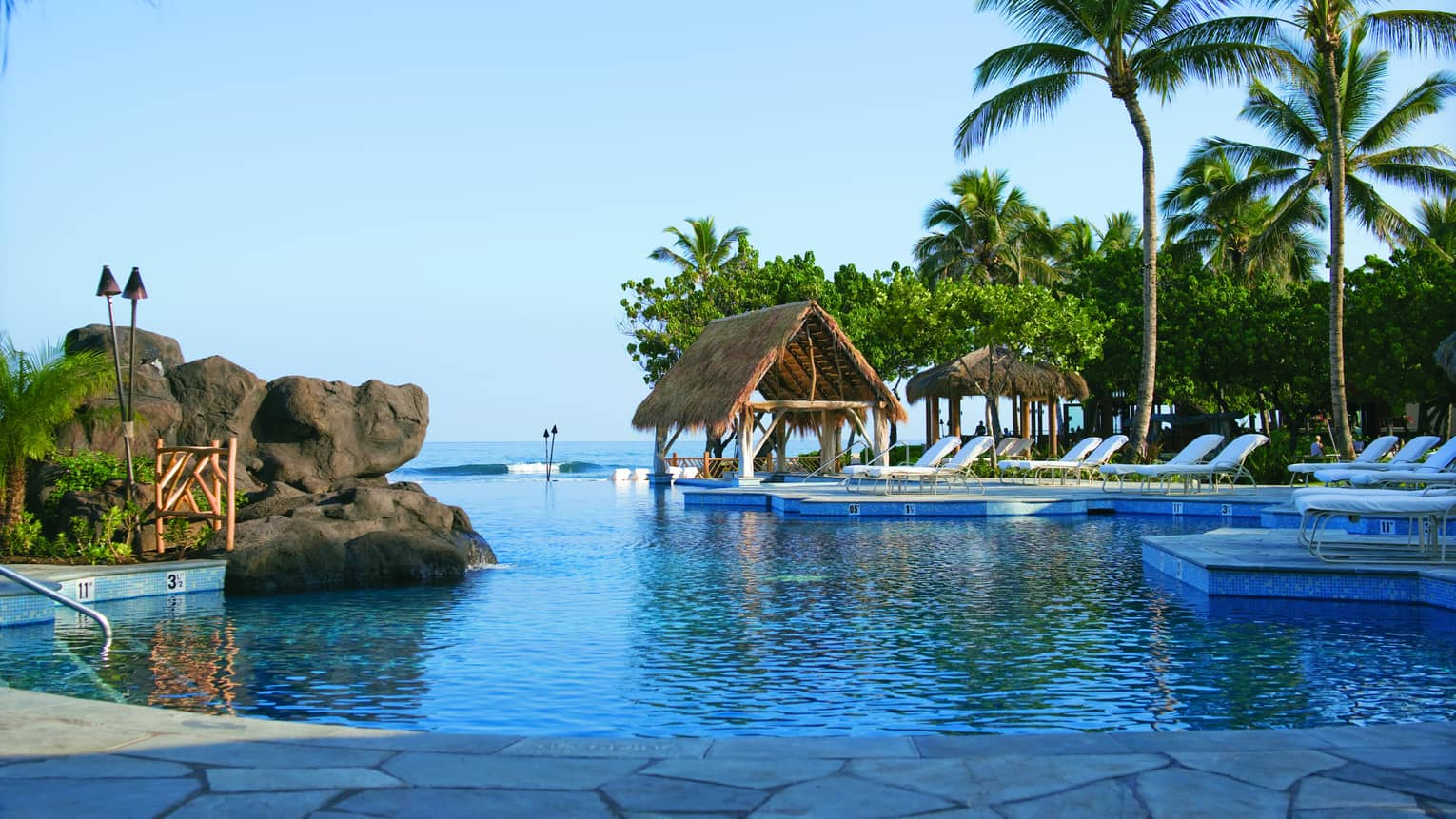 Sea Shell outdoor swimming pool with large boulders, thatched-roof hut