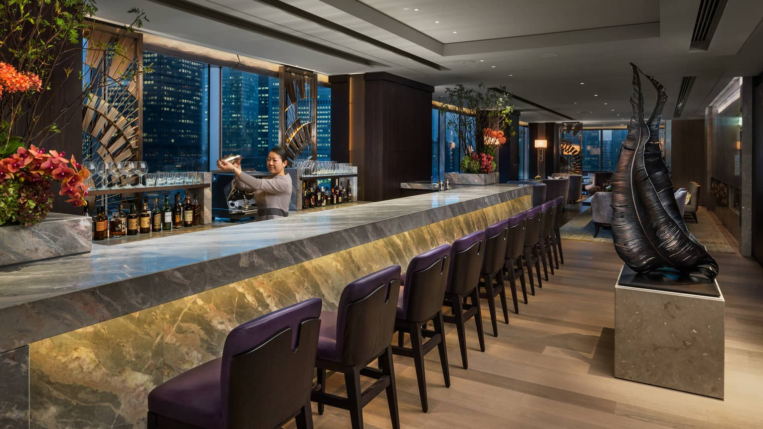 Bartender shakes silver cocktail mixer behind grey marble bar with purple stools, modern sculptures