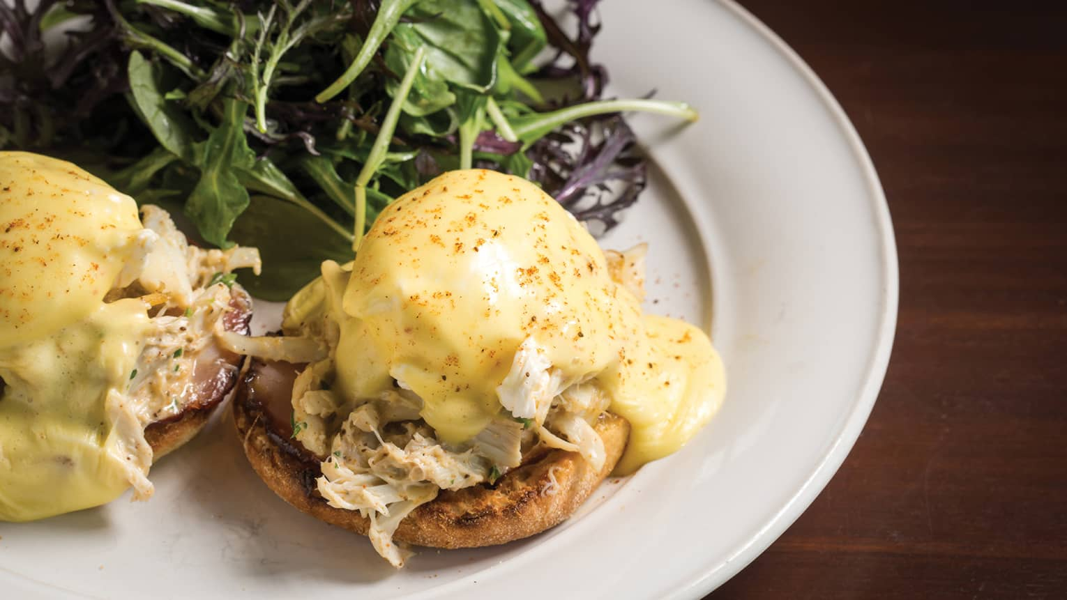 Close-up of Crab Benedict on white plate, bread with crab meat and poached egg, smothered in Hollandaise sauce