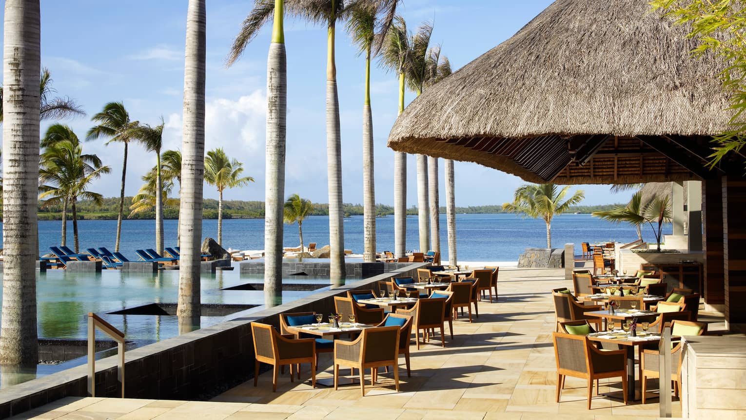 Patio dining tables by row of palms, outdoor swimming pool, thatched-roof hut