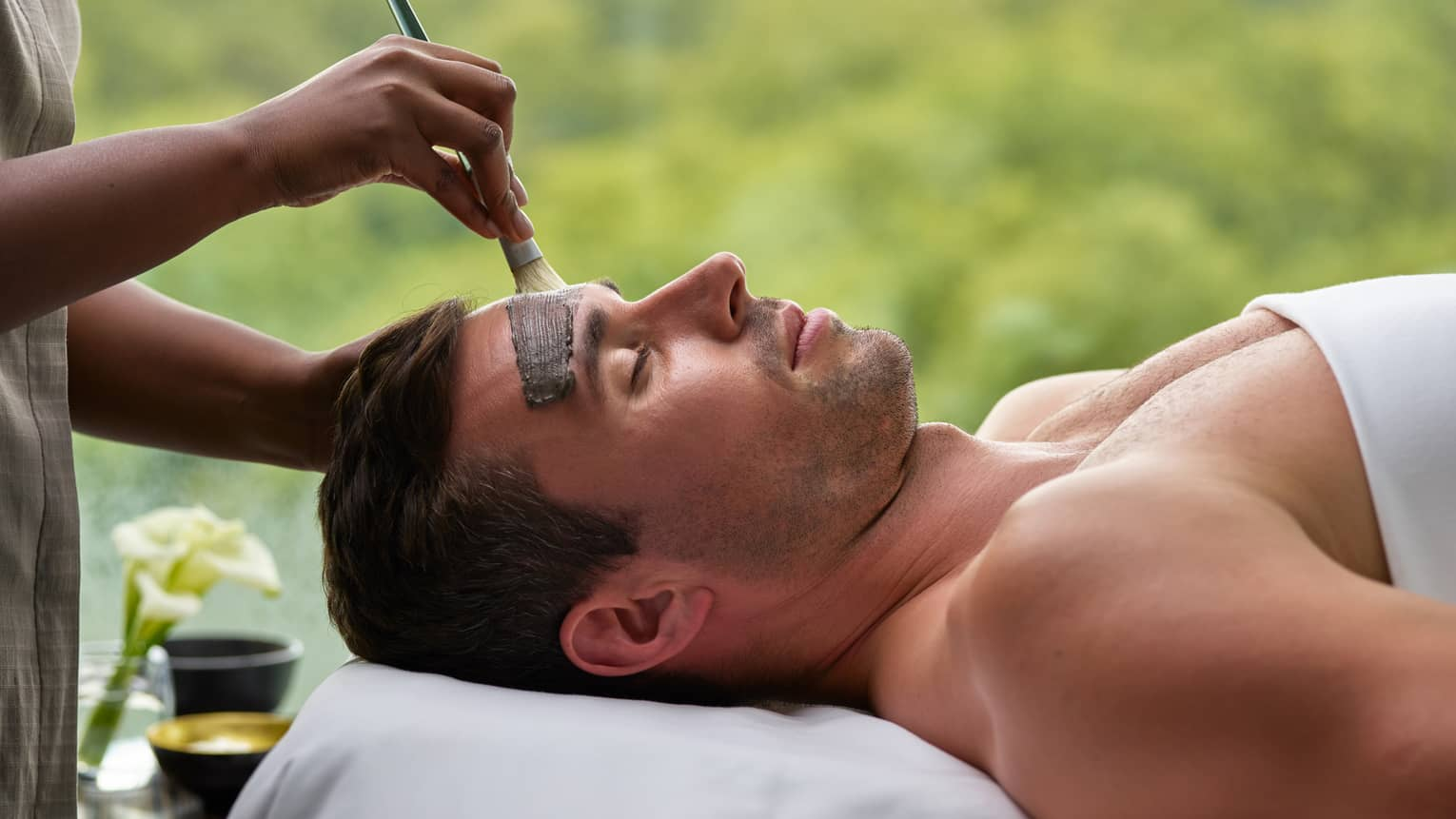 Man lying under white sheet on spa table as staff paints clay mask on his forehead