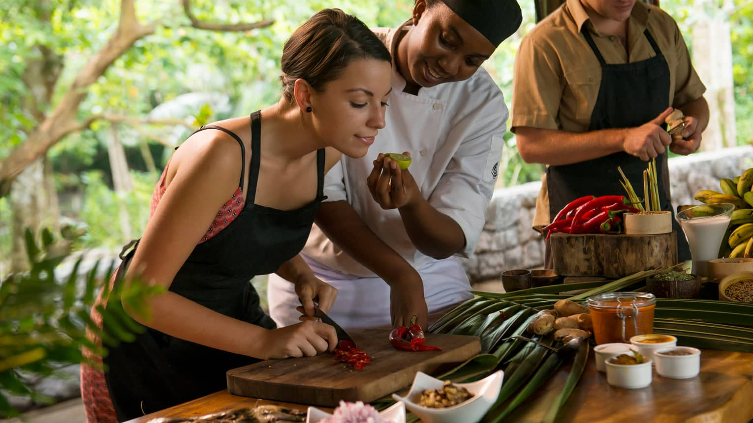 Chef holds fresh lime for woman in black apron to smell as she chops red pepper on wood board