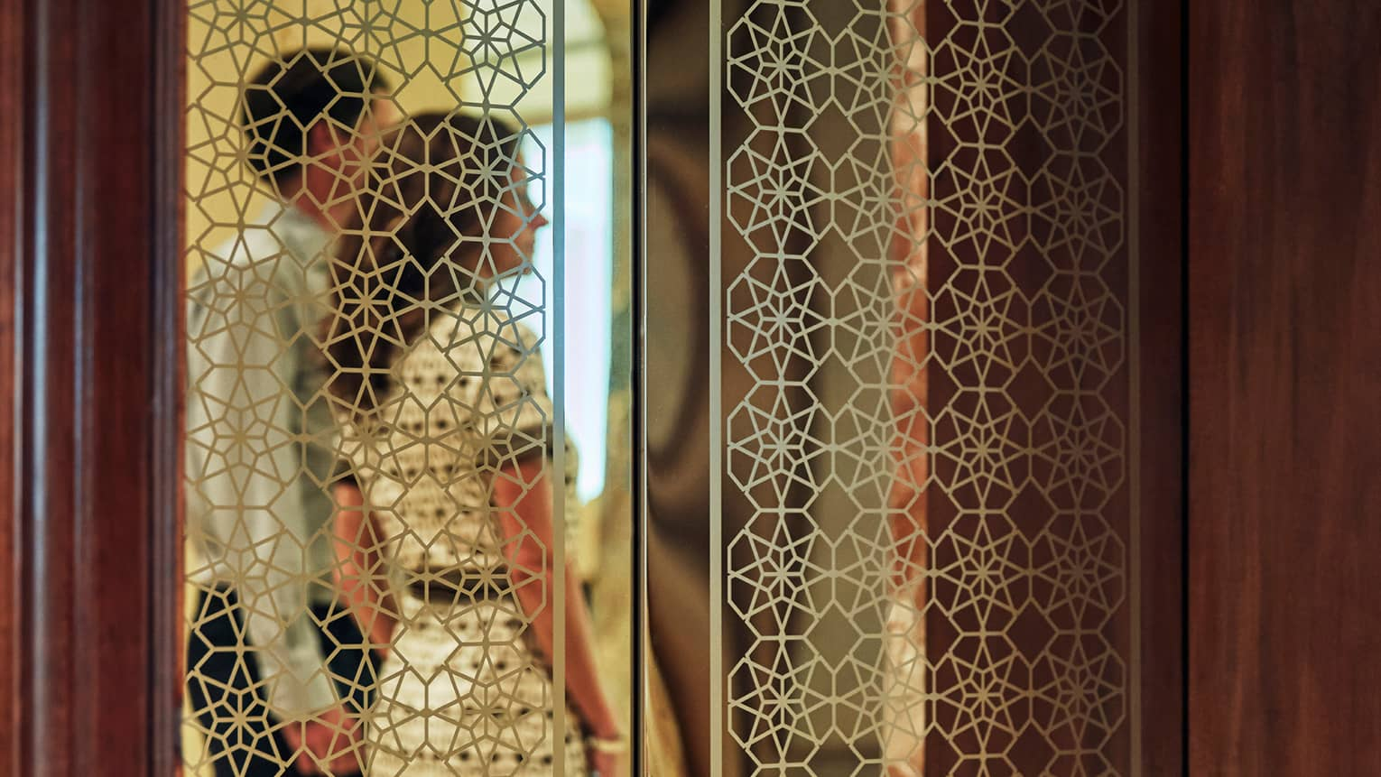 Couple behind screen with intricate gold geometric patterns, traditional Arabic design