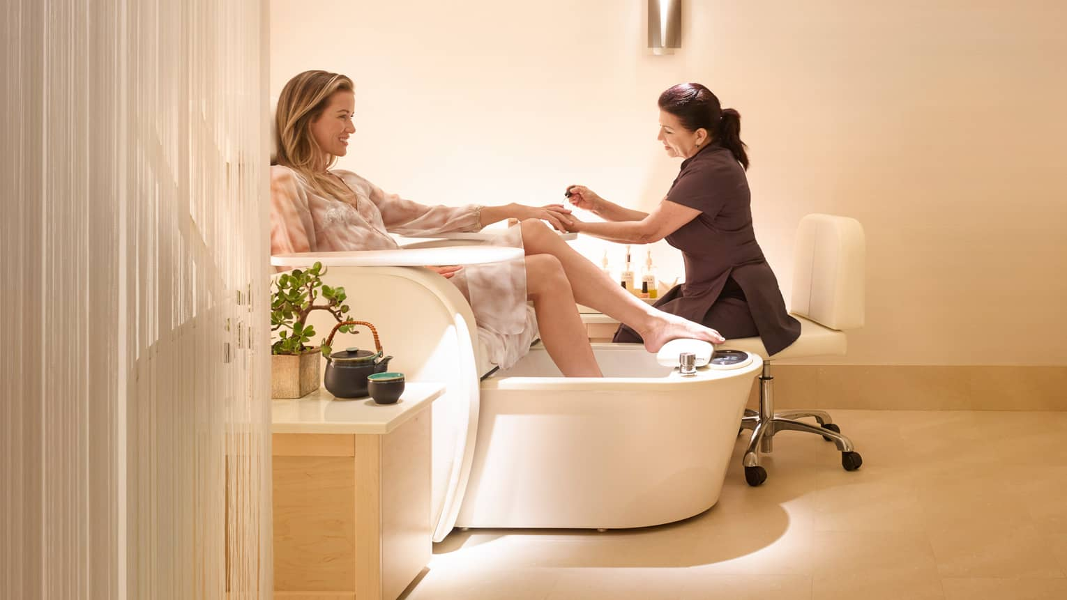 Woman wearing sheer robe soaks feet in large bath as Salon staff gives her manicure