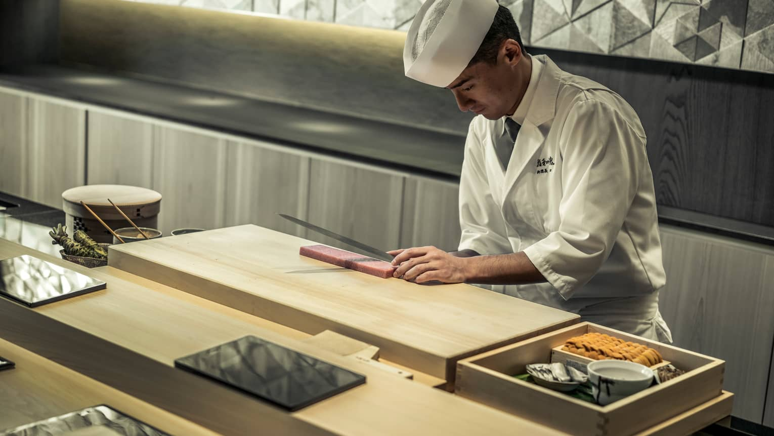 Sushi Wakon chef slices raw fish on wood board behind counter