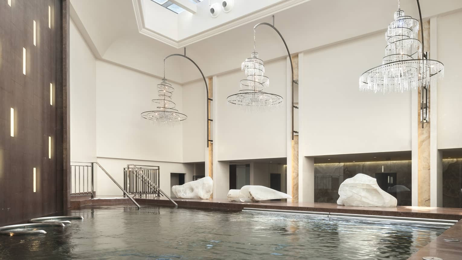 Spiral crystal chandeliers hang over pool in Luceo Spa's Aqua Zone, skylight in high ceiling