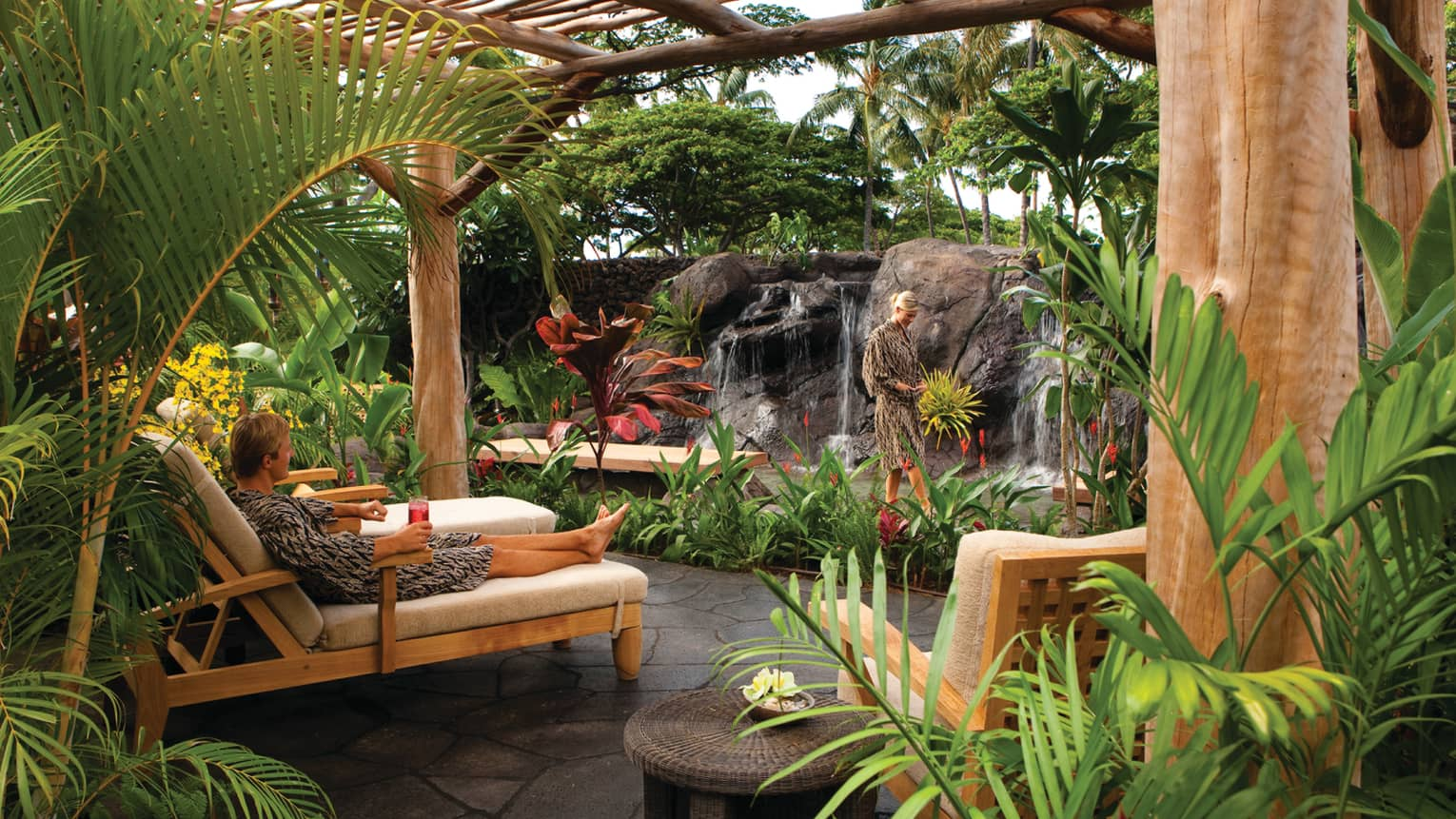 Man in robe lounges on chair with drink in Waiea tropical garden at spa