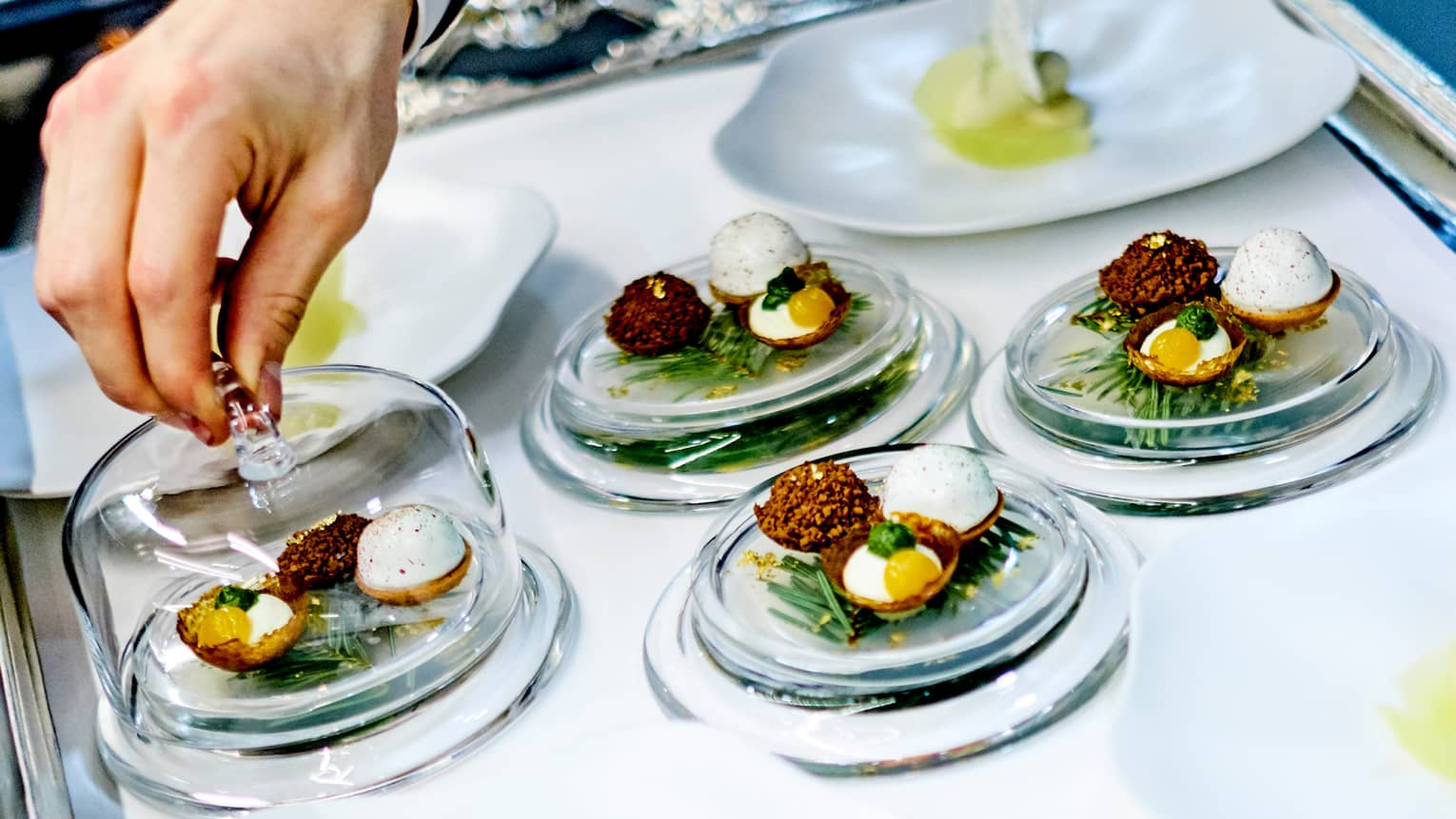Close-up of chef garnishing small egg dishes