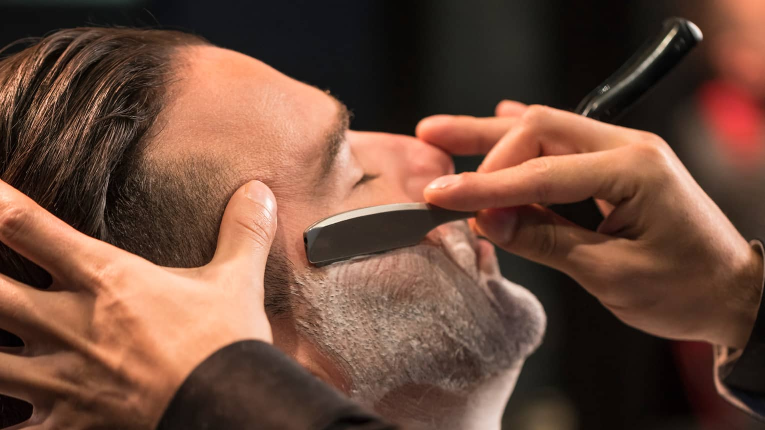 Close-up of man getting straight-razor shave in Gentlemen's Tonic barbershop