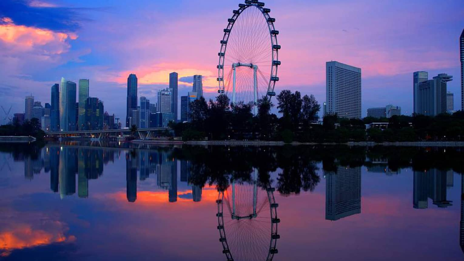 Singapore Flyer reflected in the river with the sunset in the background