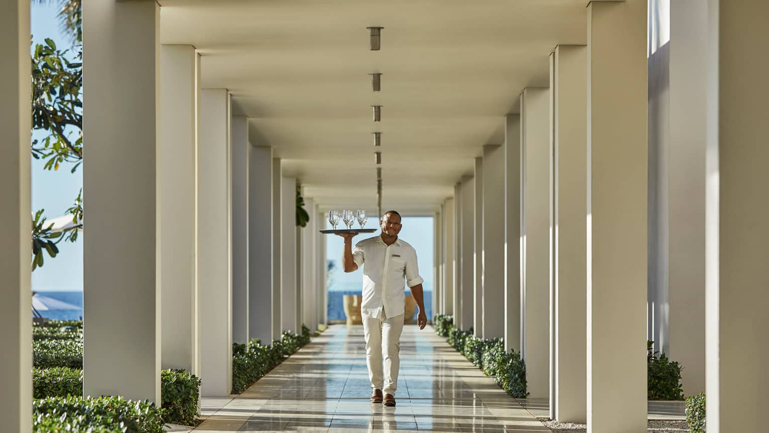 Server in white uniform carries tray of empty wine glasses through outdoor hallways with white posts, beams
