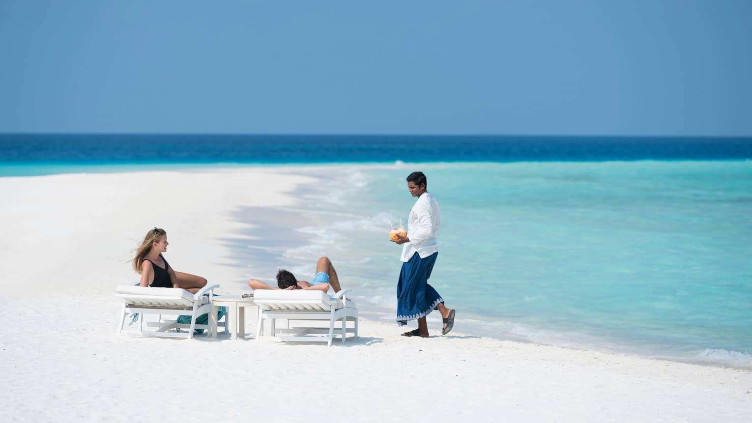 Hotel staff brings coconut cocktails to couple on lounge chairs on sand beach by ocean