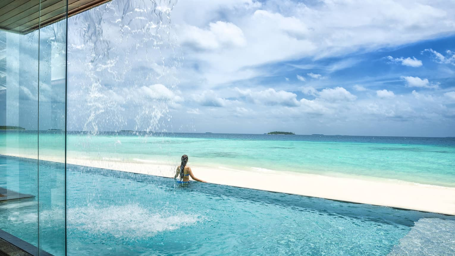 Woman stands at edge of infinity swimming pool looking out over white sand beach, blue ocean