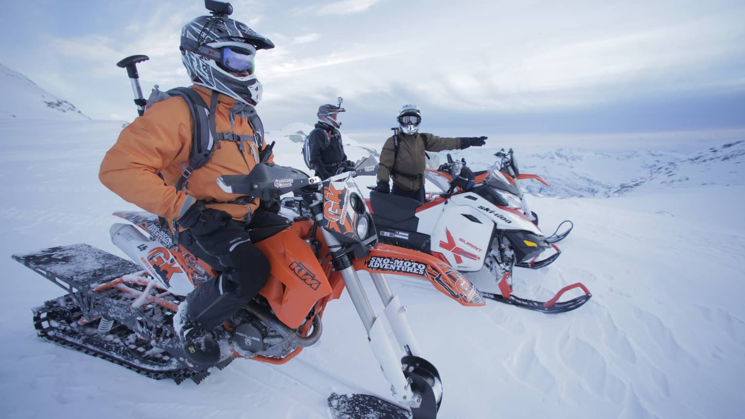 Three people wearing orange snowsuits, large helmets sit on snowmobiles, one points down mountain