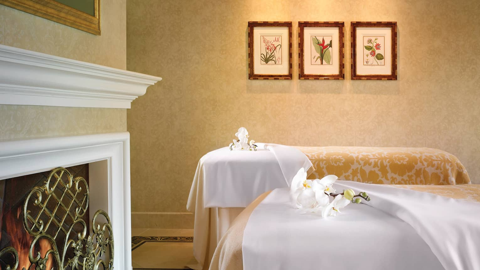 Private spa suite, two massage beds with white sheets, gold floral blankets, fresh orchids