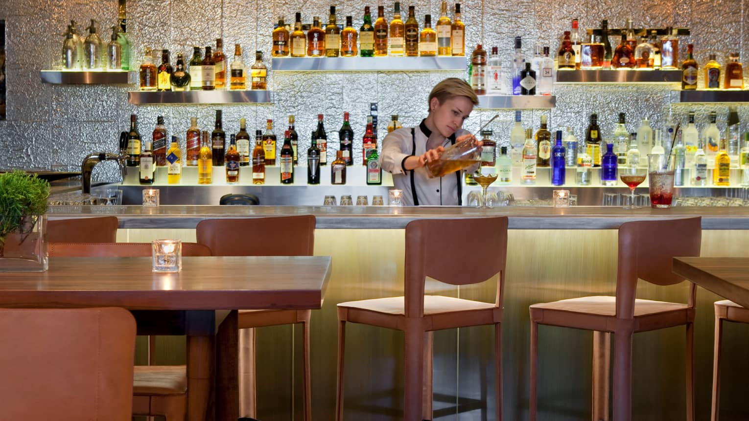 Pony Bar server pours cocktail into glass behind wood bar with stools, in front of wall of liquor bottles