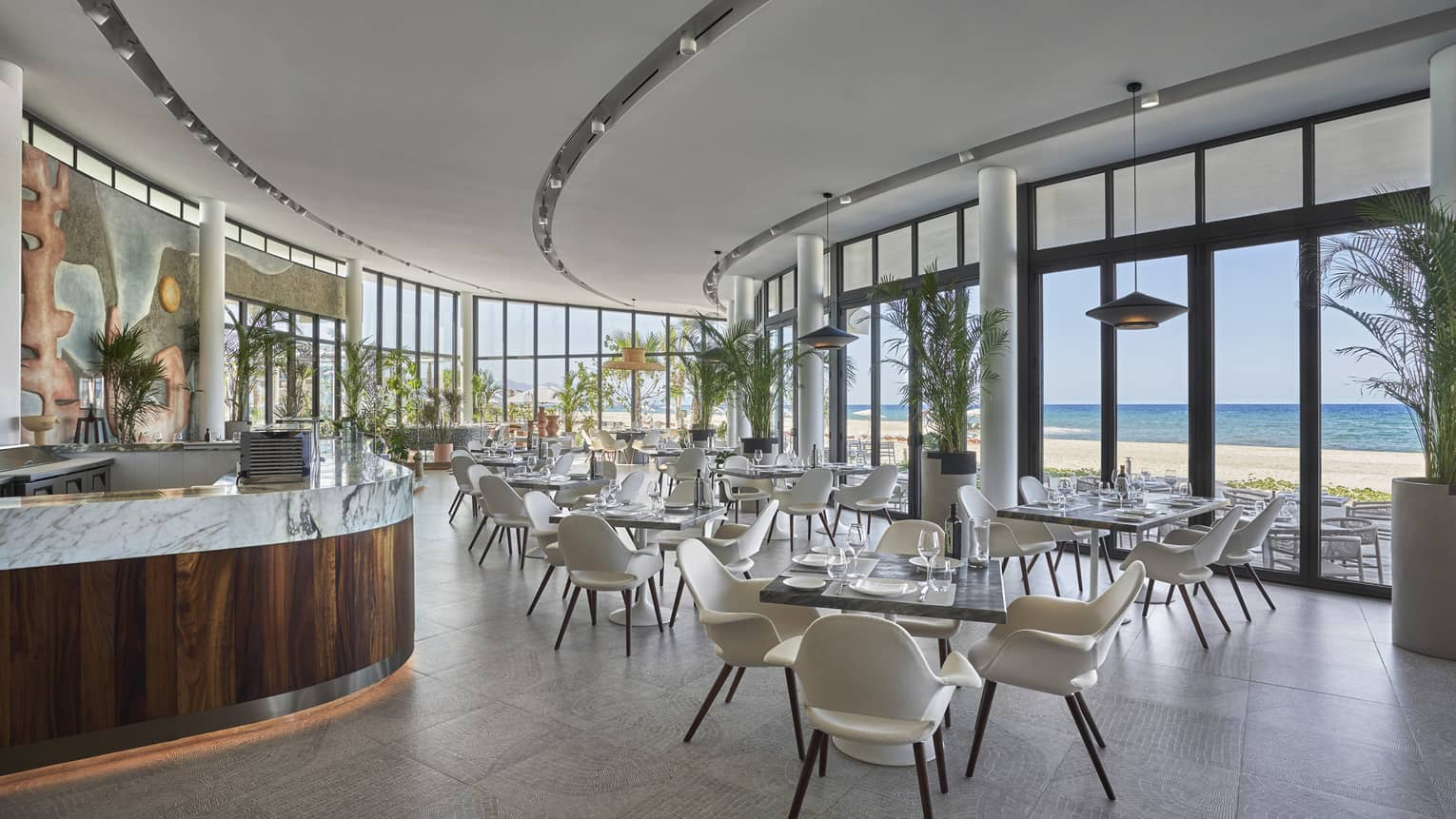 Milos contemporary curved dining room with square tables and white chairs, water views