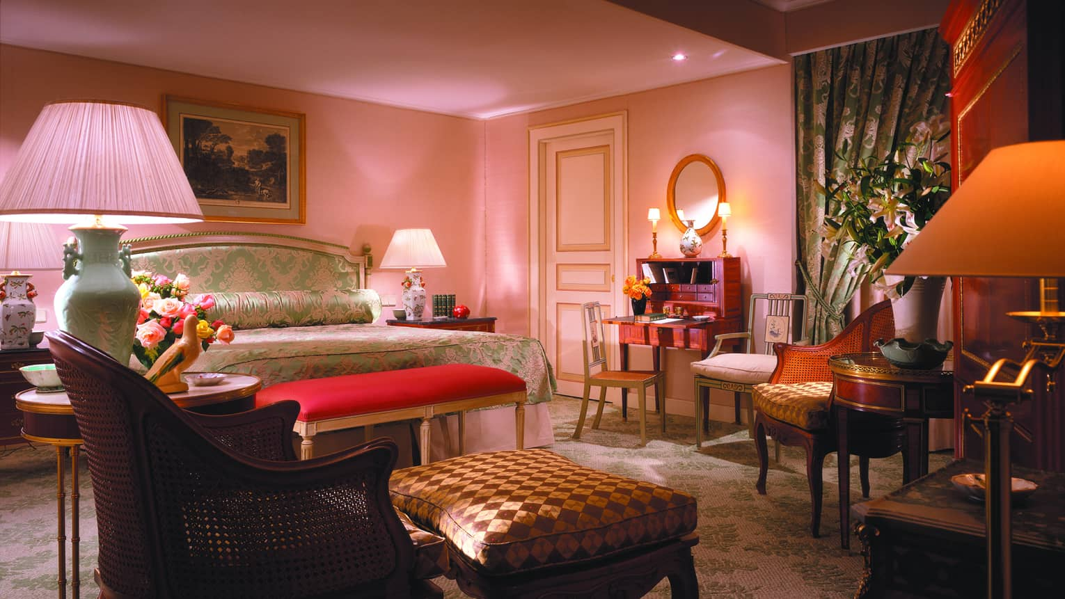 Presidential Suite with pink hues, decorative lamps and shades throughout, bright pink bench, green patterned bed linens