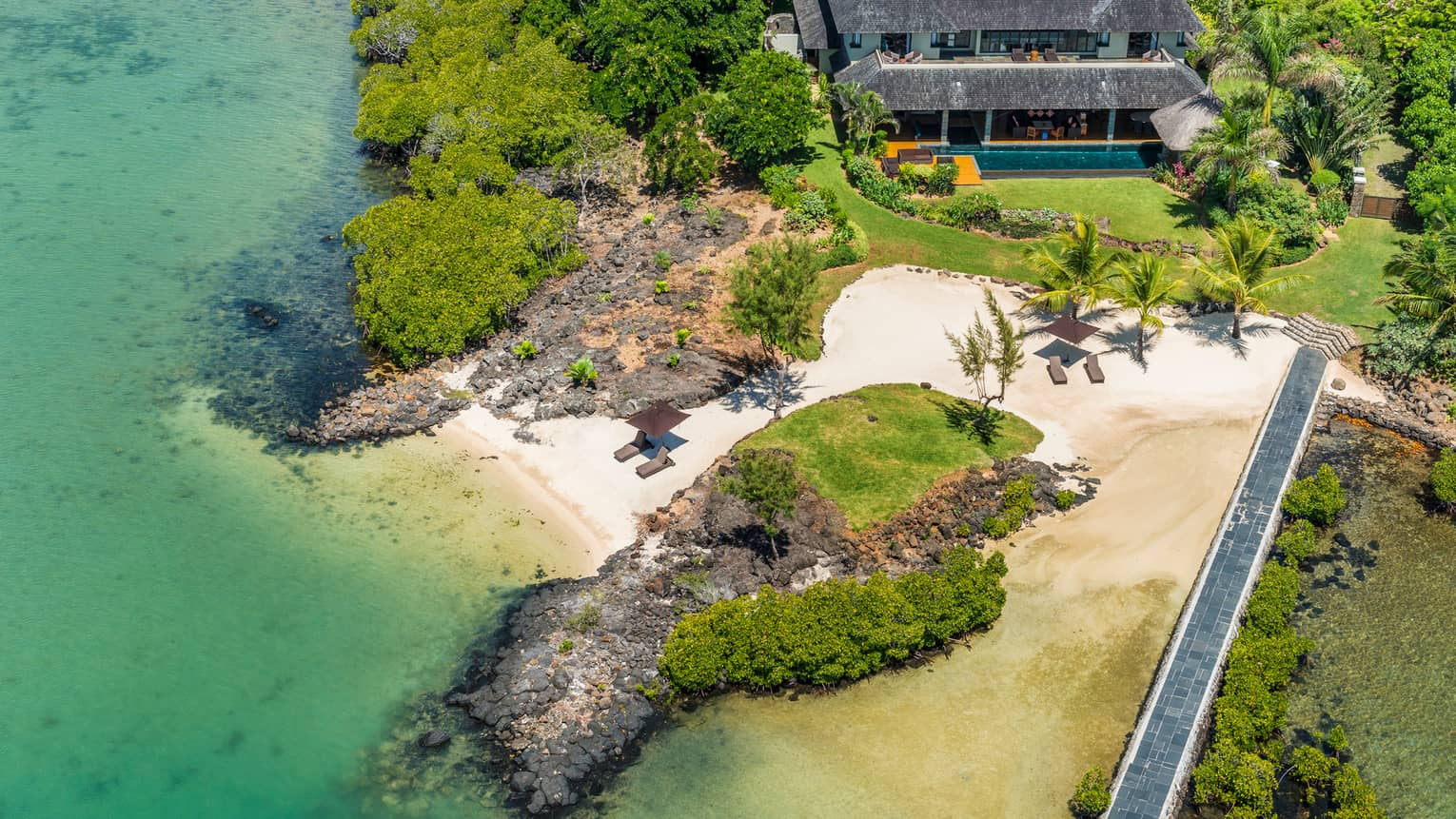 Aerial view of large, thatched-roof villa by white sand beach, large rocks on shore