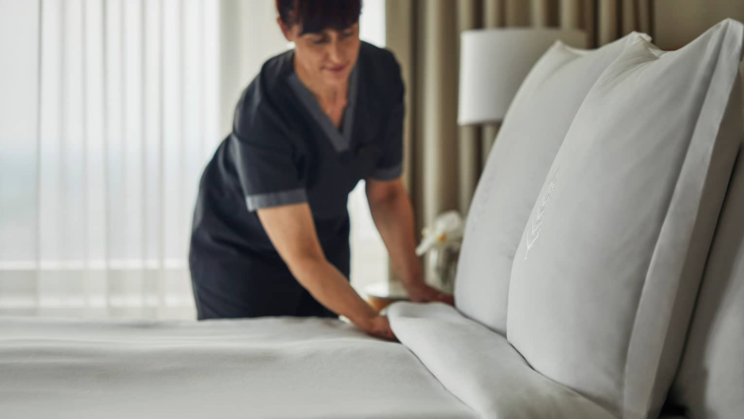 Hotel housekeeping staff makes bed, white linens and pillows