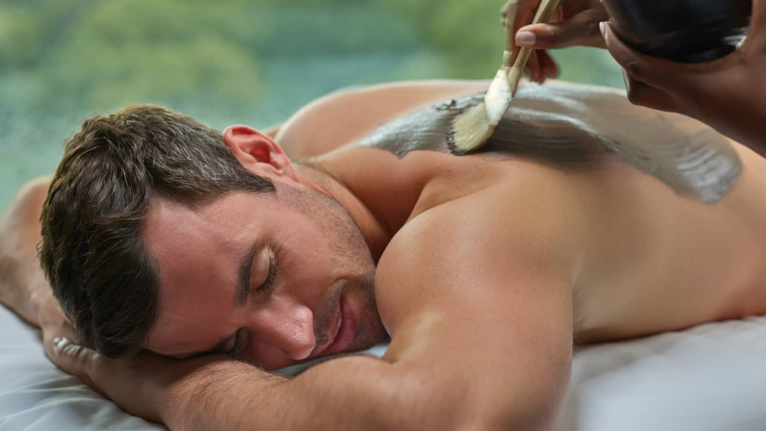 Smiling man lies on spa table as staff paint clay mask on bare back