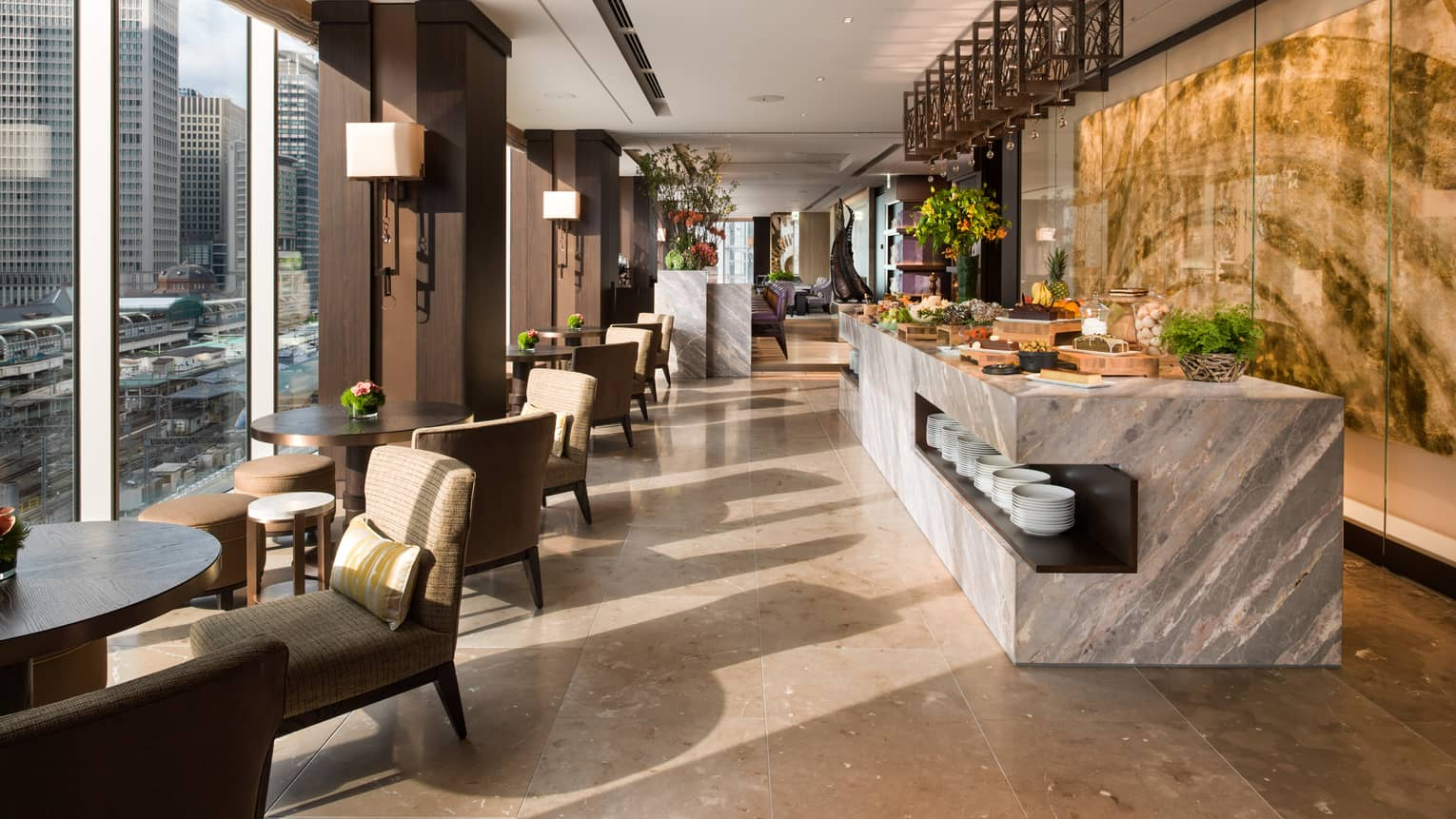 The Gastronomic Gallery with grey marble buffet, round lounge tables, chairs by sunny window