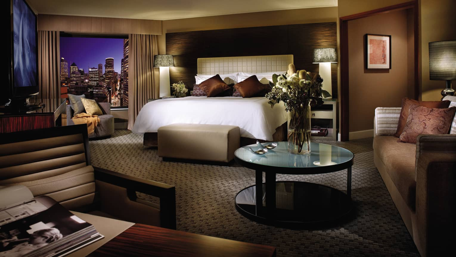 Premier City Room bed, accent pillows under ceiling lamp, city lights at night from window