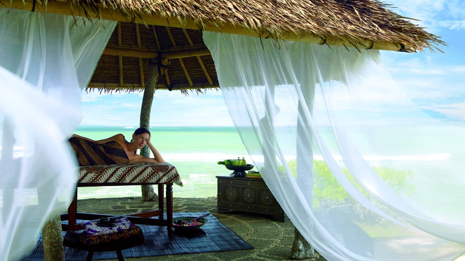 White curtains flow in the wind off thatched-roof gazebo as woman lies on massage table, gazes out at beach
