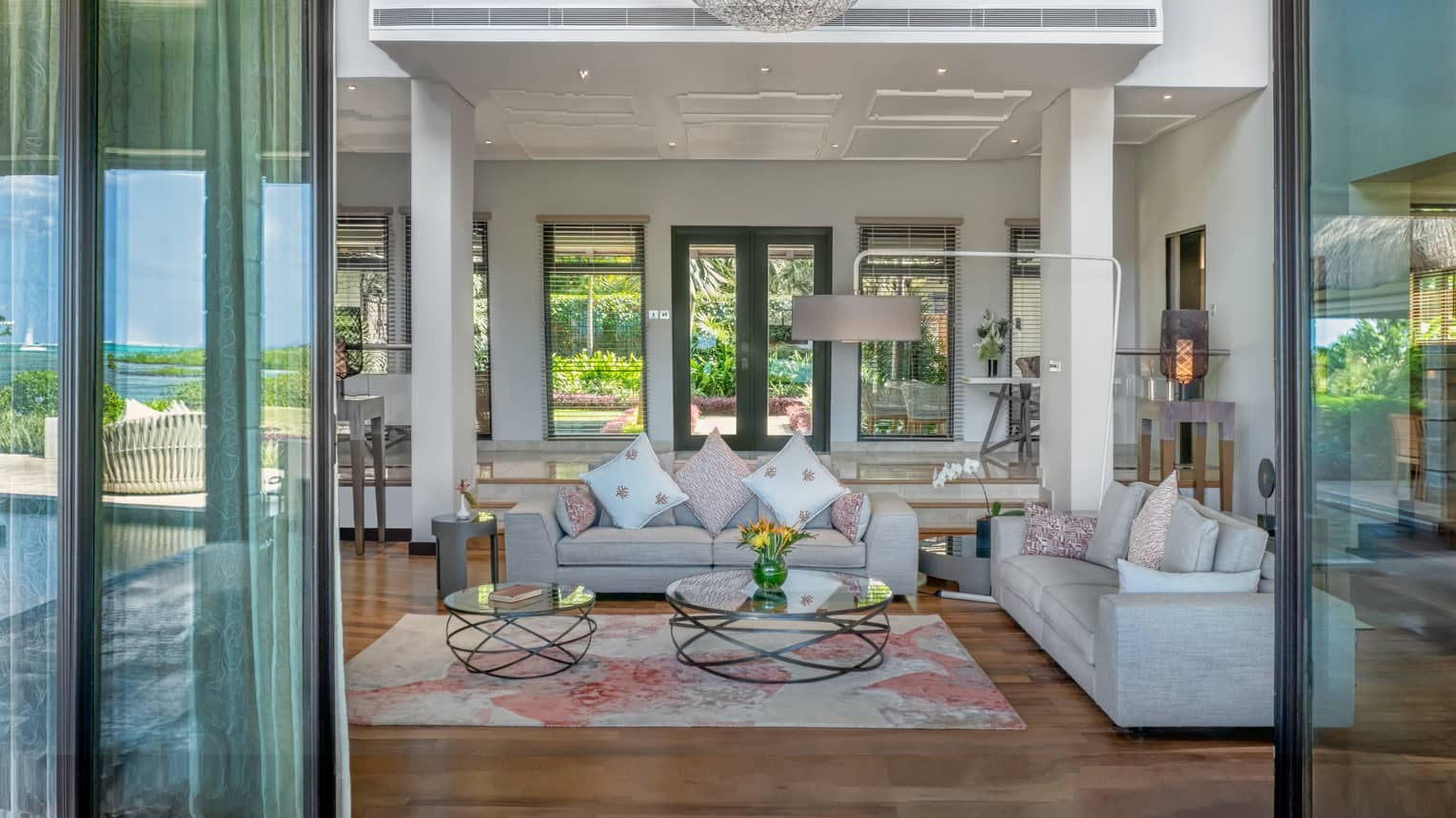 View past glass doors to living room with plush sofas, white pillars