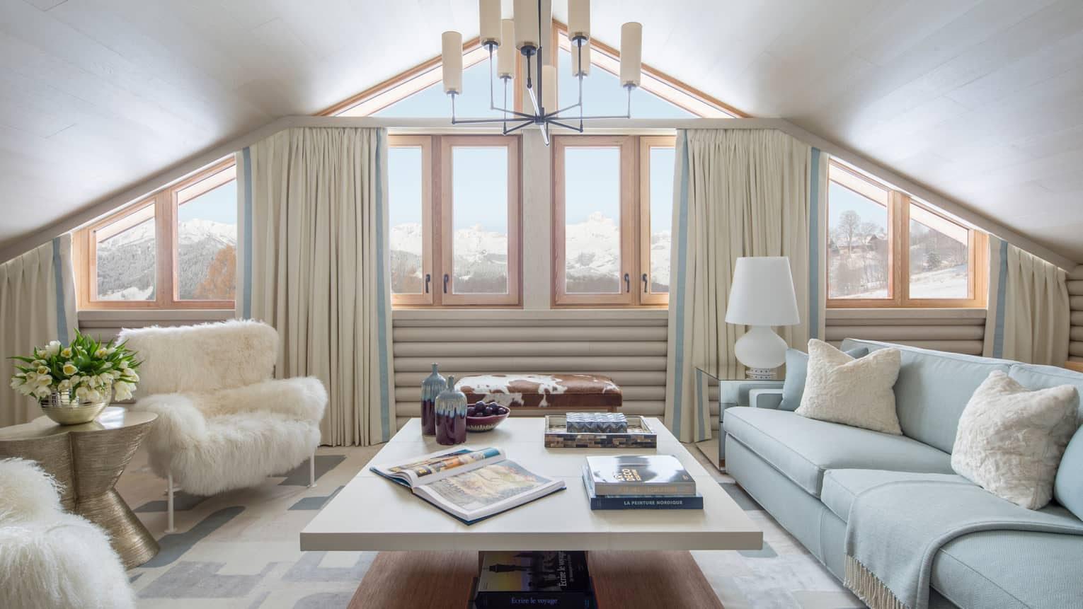 Suite Mont D'Arbois chandelier, windows under gable roof, white sofa, faux fur armchairs