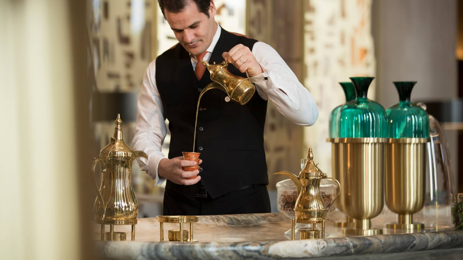 Hotel staff in vest, tie pours tea from brass pot into small cup